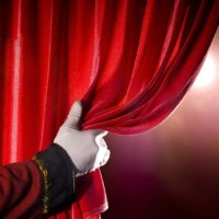 usher-opening-red-theater-curtain-with-spotlights-182176177-58b9e7333df78c353c5bf505